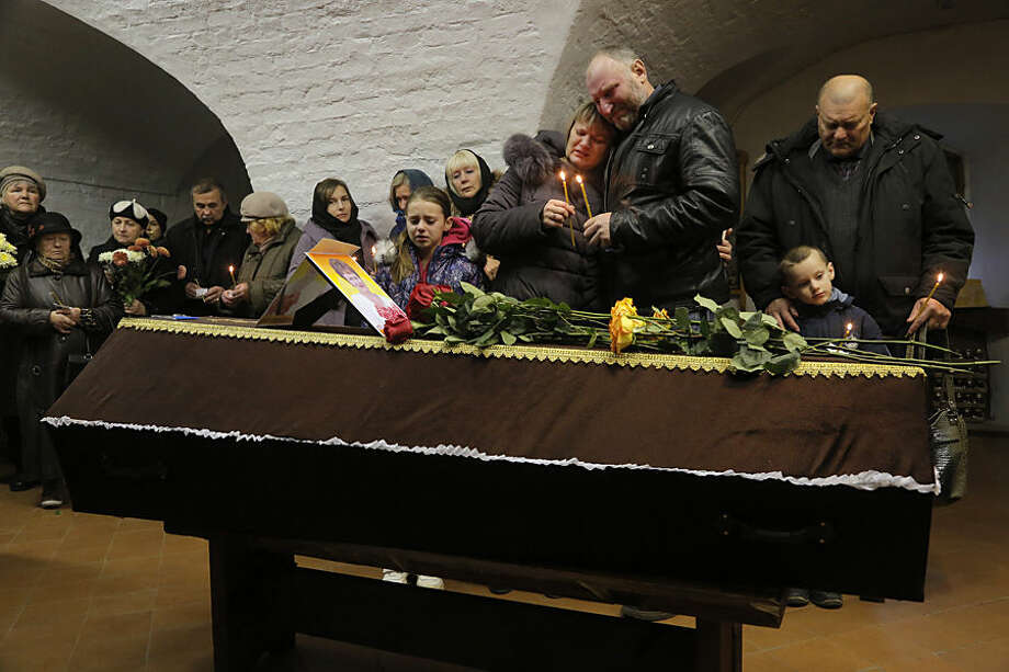 Relatives hold candles near to the coffin of Nina Lushchenko, during a religious service at a church, in Veliky Novgorod, Russia, Thursday, Nov. 5, 2015. The first victim of Saturday's plane crash in Egypt was laid to rest on Thursday following a funeral service in a medieval church in the north Russian city of Veliky Novgorod. Russia's Airbus 321-200 broke up over the Sinai Peninsula en route from the resort town of Sharm el-Sheikh to St. Petersburg, killing all 224 on board. (AP Photo/Dmitry Lovetsky)
