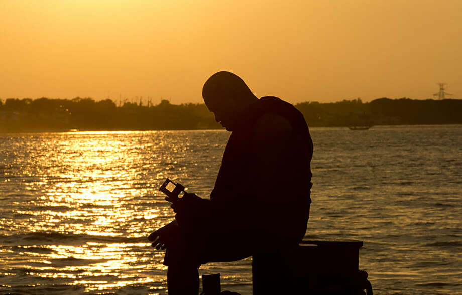A monk reads his mobile device as he waits for a ferry boat by the Yangon river at sunset in Yangon, Myanmar, Wednesday, Nov. 4, 2015. On Sunday Myanmar will hold what is being viewed as the country's best chance for a free and credible election in a quarter of a century. (AP Photo/Mark Baker)