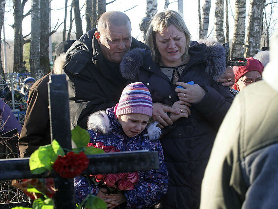 Pavel, the nephew of one of the plane crash victims Nina Lushchenko, left, reacts at her grave side with her daughter Veronika, right, and granddaughter, during her funeral at a cemetery in the village of Sitnya, 80 km (about 50 miles) of Veliky Novgorod, Russia, Thursday, Nov. 5, 2015. The first victim of Saturday's plane crash in Egypt was laid to rest on Thursday following a funeral service in a medieval church in the north Russian city of Veliky Novgorod. Russia's Airbus 321-200 broke up over the Sinai Peninsula en route from the resort town of Sharm el-Sheikh to St. Petersburg, killing all 224 on board. (AP Photo/Dmitry Lovetsky)