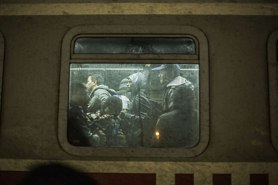 Migrants are seen while they are loaded onto a train on their way to Slovenia, at a makeshift train station within a temporary camp in Slavonski Brod, Croatia, Wednesday Nov. 4, 2015. The weather is getting colder and many migrants are not equipped to cope with prolonged periods without shelter. (AP/Manu Brabo) within a temporary camp in Slavonski Brod, Croatia, November 4, 2015 (AP/Manu Brabo)