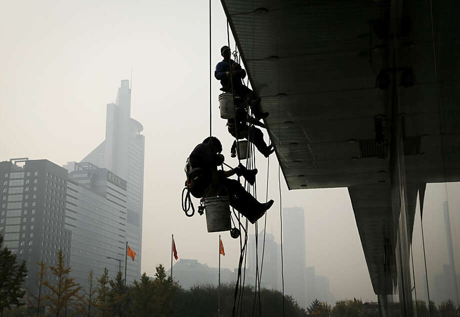 Cleaners are silhouetted against the hazy sky in Beijing, China, Wednesday, Nov. 4, 2015. Despite much publicity about efforts to battle air pollution, the problem remains at chronic levels, forcing residents to adjust to living with the haze, especially for outdoor activities. (AP Photo/Andy Wong)