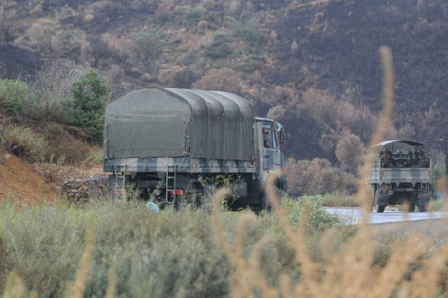Algerian military trucks are pictured in the Tizi Ouzou region, northern Algeria, on Wednesday, Sept. 23, 2014, as troops conduct search operations in the bid to find French hostage, Herve Gourdel, who was kidnapped by militants. The Algerian extremists allied with the Islamic State group have decapitated a French hostage after France carried out airstrikes in Iraq, according to a video that appeared online Wednesday. French President Francois Hollande condemned the killing of Herve Gourdel and said France would continue its fight against the Islamic State group, which are Sunni militants that have taken over large swaths of Iraq and Syria. (AP Photo)