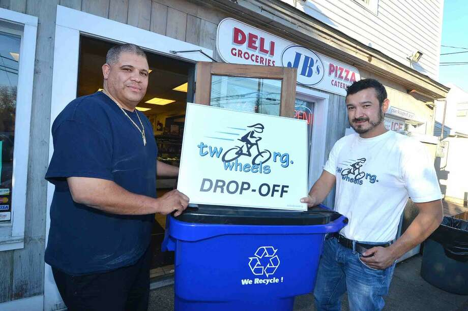 Hour Photo/Alex von Kleydorff Hector Delgado and Hector Correa with one of their Two Wheels coat drive drop off bins at the JB's Deli location