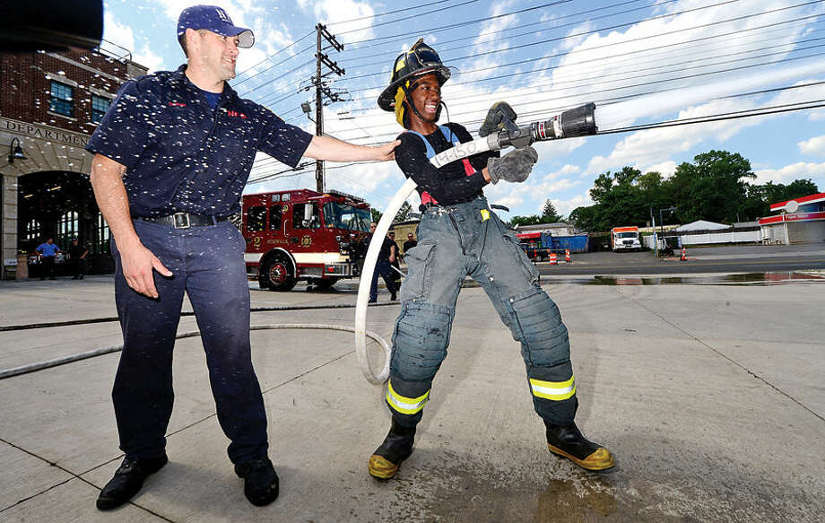 Hour photo / Erik Trautmann Briggs High School11th grader Trey Williams is helped by firefighter Colin Curran during a mock training exercise at the Norwalk Fire Department Friday as the Department begins the recruitment outreach for the next entry level test later this year. Over past four weeks, students from Briggs High School have been spending part of their Fridays at the Norwalk Fire Department to learn about firefighting as a career opportunity.