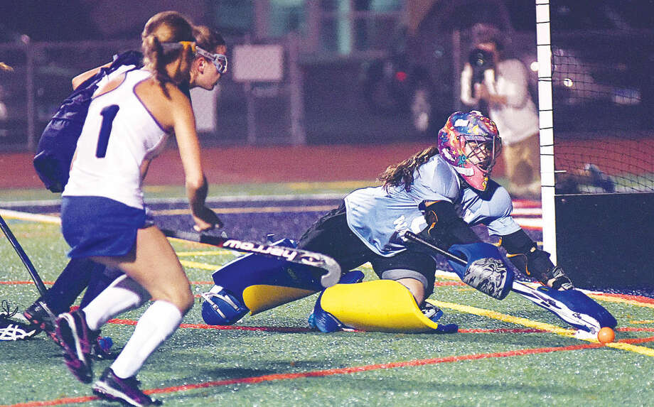 Hour photo/John Nash - Wilton goalie Amanda Hendry dives to try and deflect a shot during Thursday's FCIAC field hockey championship game against Darien at Casagrande Field in Norwalk. Darien won 1-0.