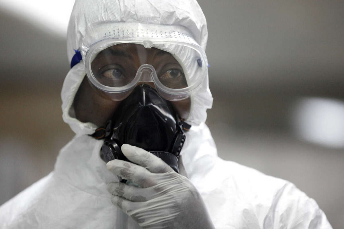 FILE - In this Aug. 4, 2014, file photo, a Nigerian health official wearing a protective suit waits to screen passengers for the Ebola virus at the arrivals hall of Murtala Muhammed International Airport in Lagos, Nigeria. Six months into the biggest-ever Ebola outbreak, scientists say they've learned more about how the potentially lethal virus behaves and how future outbreaks might be stopped. The first cases of Ebola were reported in Guinea by the World Health Organization on March 23 before spreading to Sierra Leone, Liberia and elsewhere. (AP Photo/Sunday Alamba, File)