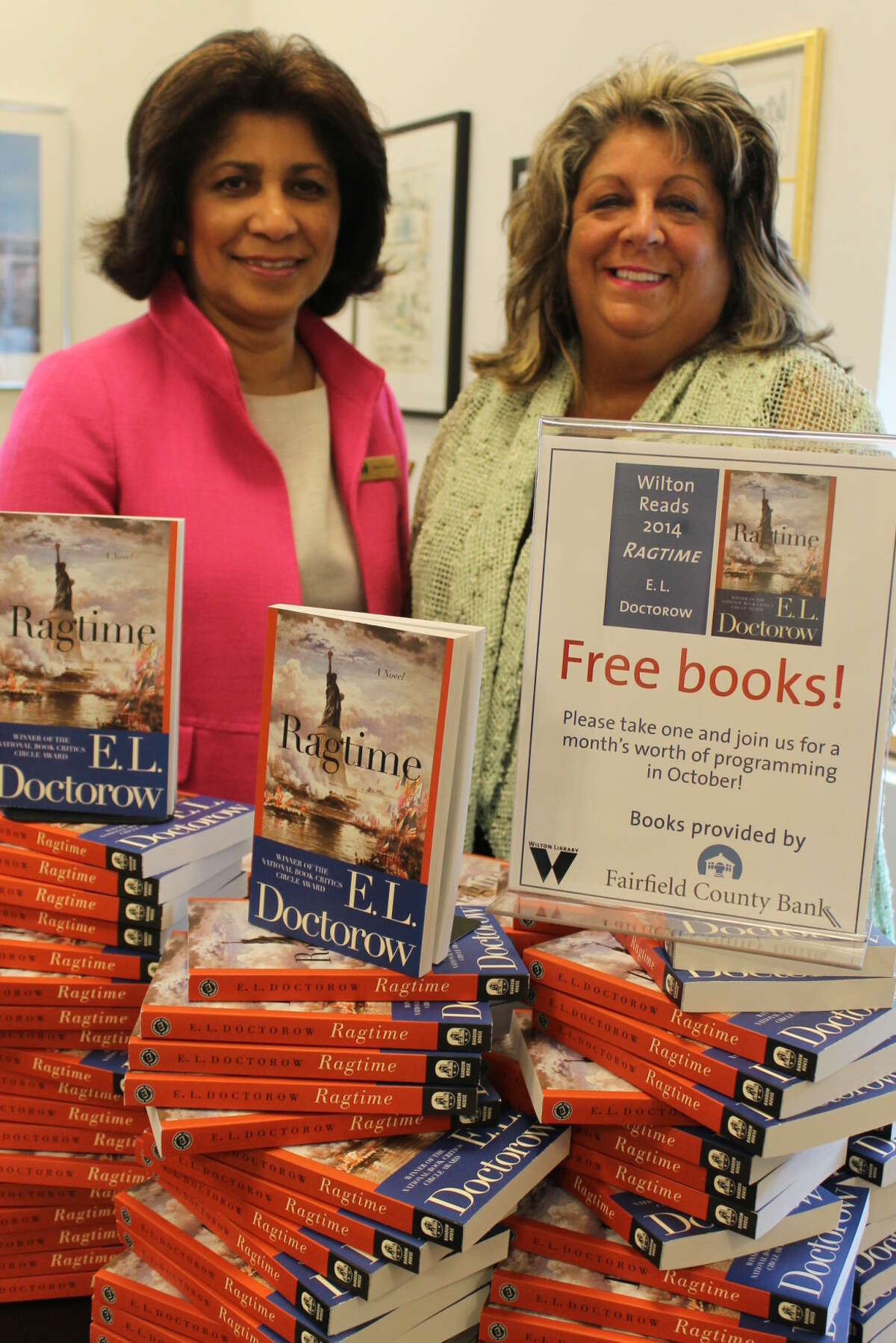 """Elaine Tai-Lauria, executive director of Wilton Library, and Carol Johnson, vice president of Fairfield County Bank, display free copies of the novel """"Ragtime,"""" which will be given out on Saturday, Sept. 27 at the library in advance of the month-long Wilton Reads program in October. For more information, visit www.wiltonlibrary.org or call (203) 7672-3950, ext. 213."""