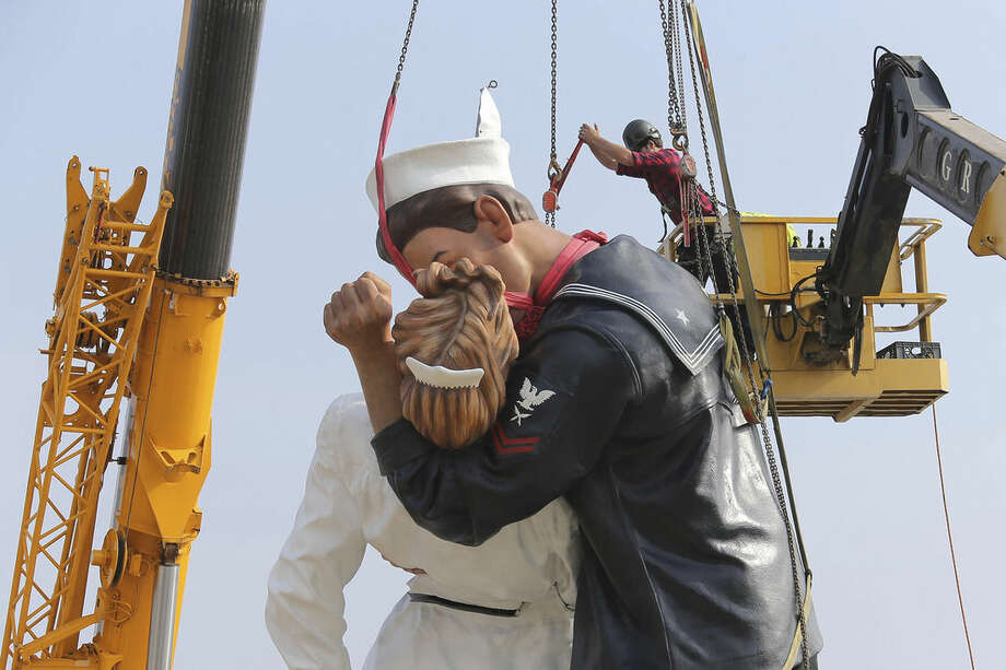 "Workers prepare to lift a piece of ""Unconditional Surrender,"" an 8-meter (25-foot) cast-bronze sculpture in color of a sailor and a nurse in lip-locked embrace, outside the Caen Memorial in Normandy, France, Tuesday, Sept. 23, 2014. The sculpture by Seward Johnson is based on a U.S. Navy photographer's black-and-white snapshot taken on Aug. 15, 1945, according to the Sculpture Foundation, a U.S.-based nonprofit that owns the work. It also resembles a famous photograph taken by Life magazine Alfred Eisenstaedt on that day. The sculpture is to spend a year outside the Caen Memorial, a museum focusing on World War II. (AP Photo/David Vincent)"