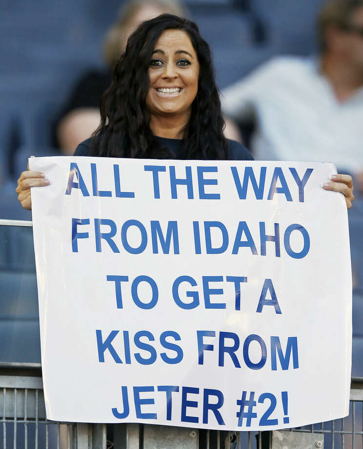 Tanya Lopez of Fruitland, Idaho, holds up a handmade sign while watching the New York Yankees batting practice before the Yankees baseball game against the Baltimore Orioles at Yankee Stadium in New York, Monday, Sept. 22, 2014. The Yankees opened batting practice to the public for the Yankees final home stand. Derek Jeter's final home game is Thursday. (AP Photo/Kathy Willens)