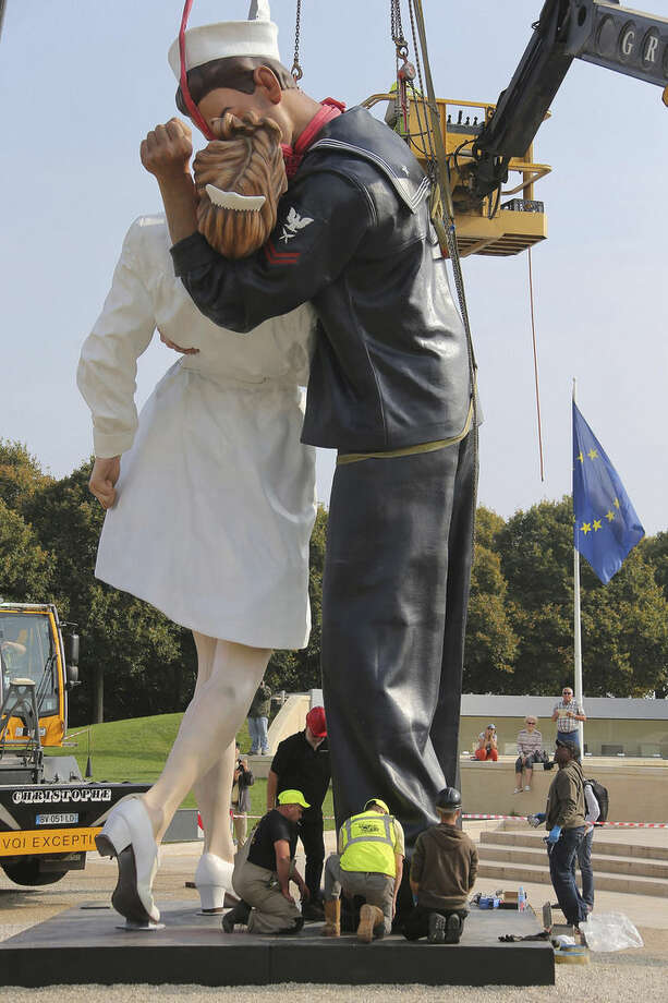 "Workers hoist and lock together pieces of ""Unconditional Surrender,"" an 8-meter (25-foot) cast-bronze sculpture in color of a sailor and a nurse in lip-locked embrace, outside the Caen Memorial in Normandy, France, Tuesday, Sept. 23, 2014. The sculpture by Seward Johnson is based on a U.S. Navy photographer's black-and-white snapshot taken on Aug. 15, 1945, according to the Sculpture Foundation, a U.S.-based nonprofit that owns the work. It also resembles a famous photograph taken by Life magazine Alfred Eisenstaedt on that day. The sculpture is to spend a year outside the Caen Memorial, a museum focusing on World War II. (AP Photo/David Vincent)"
