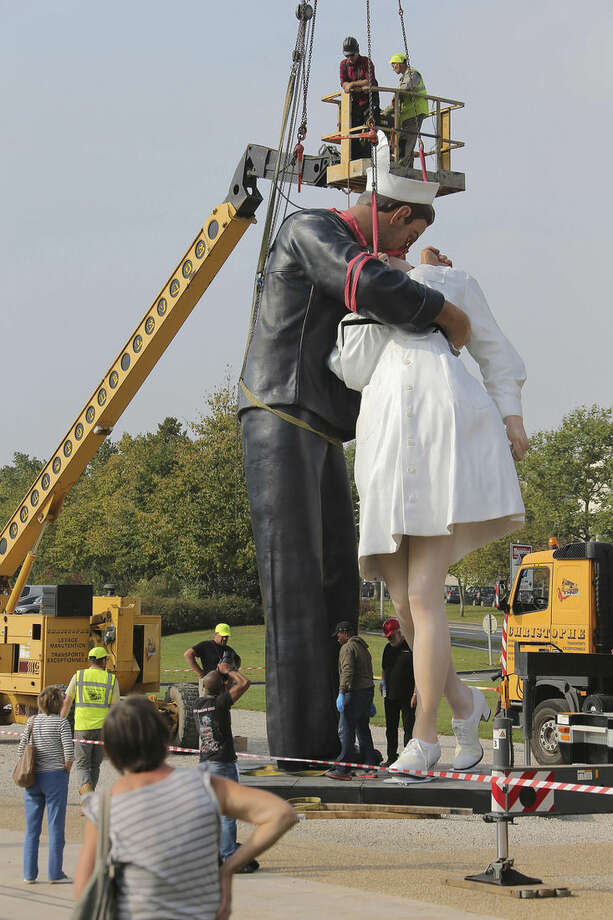 """Workers hoist and lock together pieces of """"Unconditional Surrender,"""" an 8-meter (25-foot) cast-bronze sculpture in color of a sailor and a nurse in lip-locked embrace, outside the Caen Memorial in Normandy, France, Tuesday, Sept. 23, 2014. The sculpture by Seward Johnson is based on a U.S. Navy photographer's black-and-white snapshot taken on Aug. 15, 1945, according to the Sculpture Foundation, a U.S.-based nonprofit that owns the work. It also resembles a famous photograph taken by Life magazine Alfred Eisenstaedt on that day. The sculpture is to spend a year outside the Caen Memorial, a museum focusing on World War II. (AP Photo/David Vincent)"""