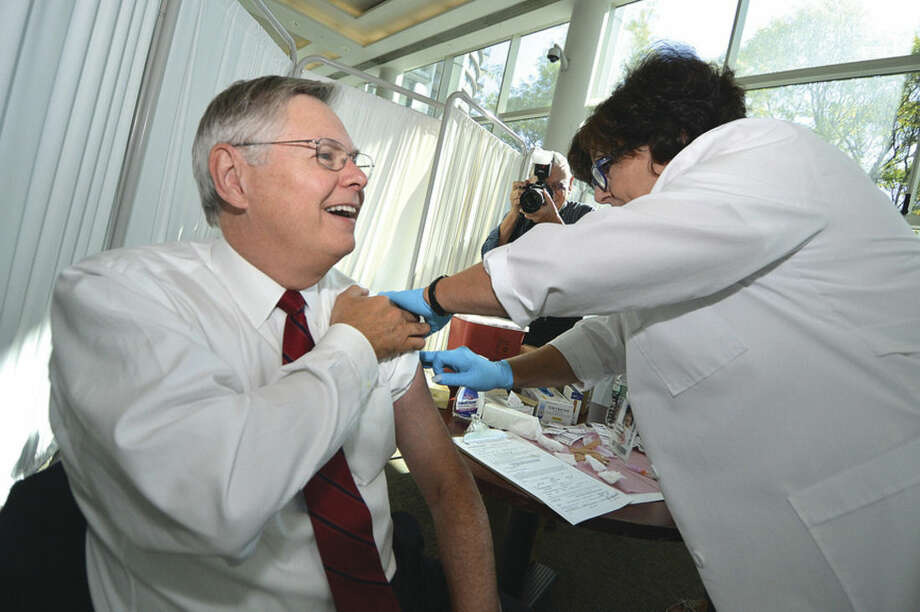 Hour Photo/Alex von KleydorffMayor David Martin gets his flu shot from City of Stamford Public Health Nurse Lynn Galgano at Fight The Flu campaign kickoff at City Hall on Tuesday.