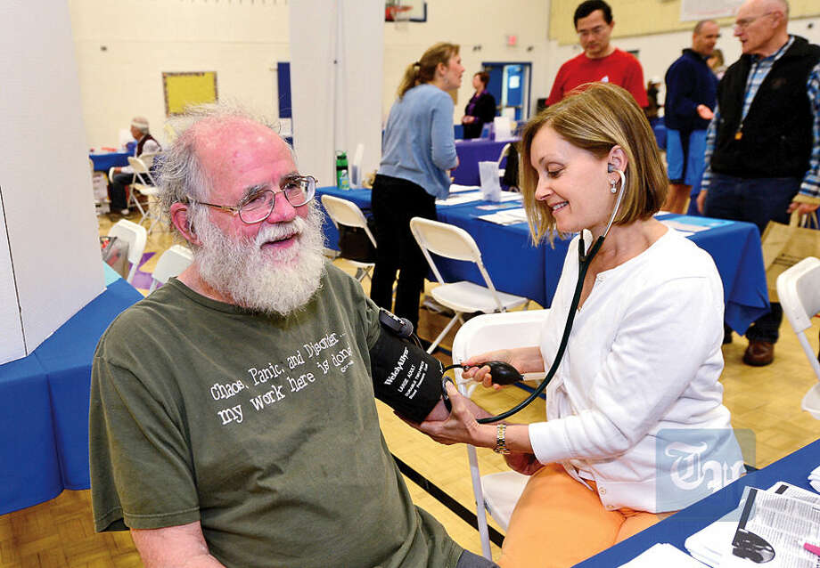 John Iles gets his blood pressure taken from Norwalk Hospital nurse practitioner Janet Kranes during The Hour Publishing Co. and Western Connecticut Health Network annual Health & Wellness Fair at Wilton Family Y Saturday.