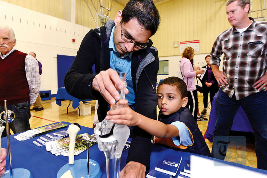 Arav Gupta 5, and his dad Vivek Gupta look at a prosthetic knee during The Hour Publishing Co. and Western Connecticut Health Network annual Health & Wellness Fair at Wilton Family Y Saturday.