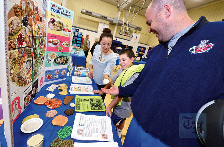 Nico Matik and his dad David get nutrition advice from Dietetic Intern Kelly Gruber during The Hour Publishing Co. and Western Connecticut Health Network annual Health & Wellness Fair at Wilton Family Y Saturday.