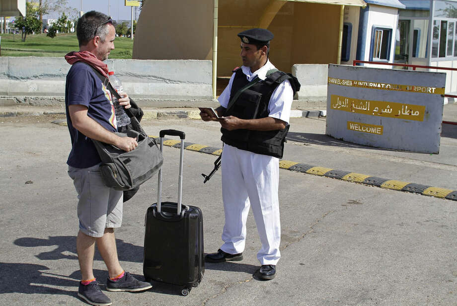 An Egyptian policeman checks a Russian tourist's passport at the main entrance to the Sharm el-Sheikh airport in Egypt on Saturday, Nov. 7, 2015. Egypt's Foreign Minister Sameh Shoukry complained on Saturday that Western governments had not sufficiently helped Egypt in its war on terrorism and had not shared relevant intelligence with Cairo regarding the Russian airplane that crashed last week in the Sinai, killing all 224 people onboard. (AP Photo/Ahmed Abd El-Latif)