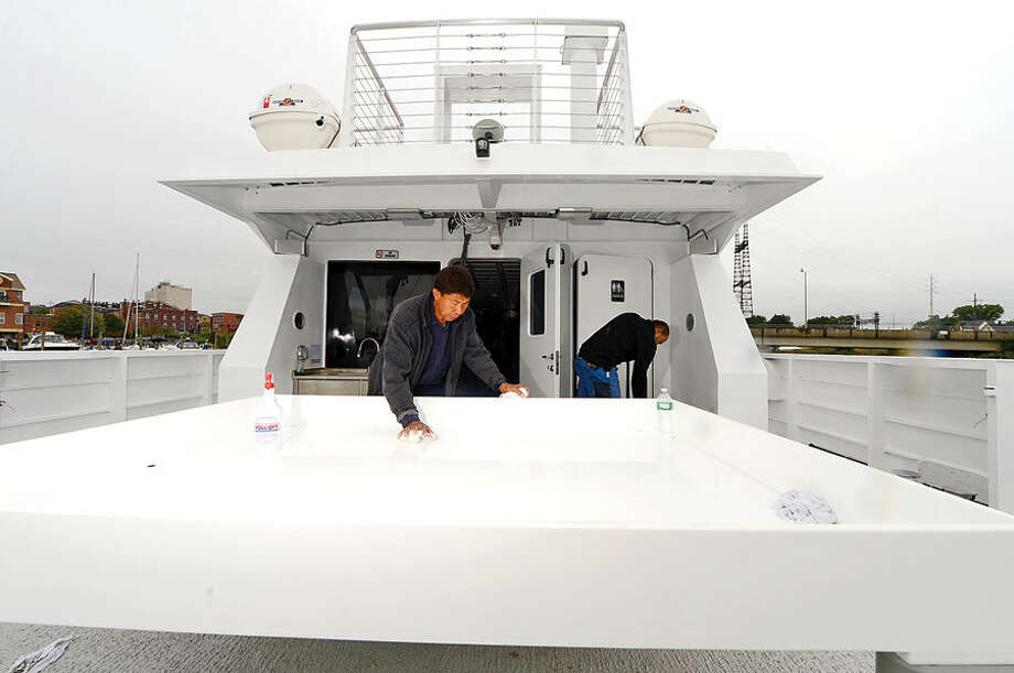 "Hour photo / Erik Trautmann Workers with vessel manufacturer Robert E. Derecktor Inc. including Antonio Brito readies the Martime Aquarium's new research vessel, R/V Spirit of the Sound for it's christening on Friday. The 65-foot catamaran is bigger, quieter and ""greener"" than the current research vessel. She will be the only research vessel in the country with a hybrid-electric propulsion system, so the vessel runs silently and significantly reduce fuel costs. The R/V Spirit of the Sound will double capacity for programming on the water from 29 to 60 participants per cruise."