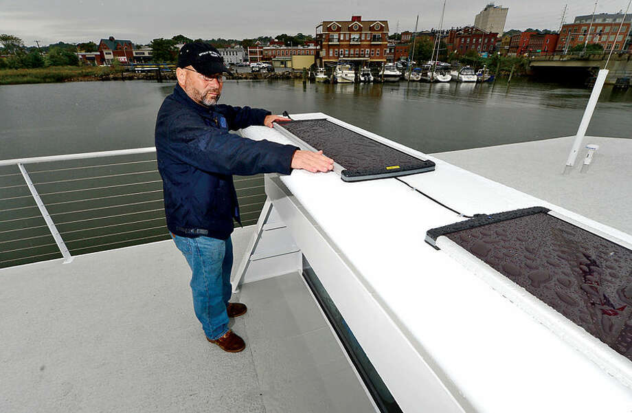"Hour photo / Erik Trautmann Alternative Marine Technologies' Barry Natale inspects the solar panels on the Martime Aquarium's new research vessel, R/V Spirit of the Sound. The 65-foot catamaran is bigger, quieter and ""greener"" than the current research vessel. She will be the only research vessel in the country with a hybrid-electric propulsion system, so the vessel runs silently and significantly reduce fuel costs. The R/V Spirit of the Sound will double capacity for programming on the water from 29 to 60 participants per cruise."