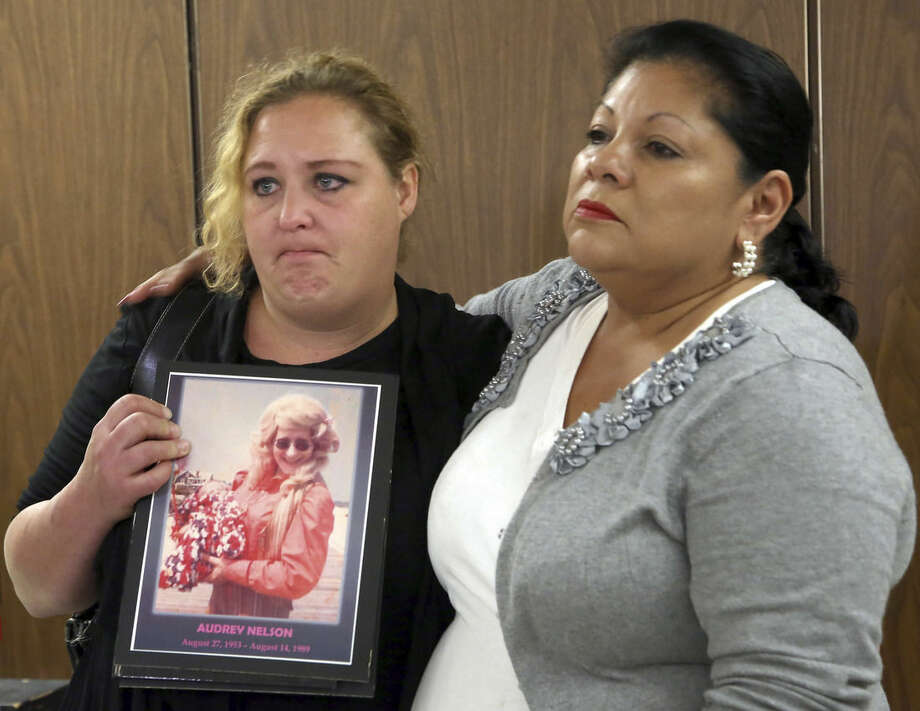 Pearl Nelson, left, holds a photo of her late mother Audrey Nelson, a victim of serial killer Samuel Little, with Mary Louise Frias, goddaughter of another victim, Guadalupe Apodaca Zambrano, during a news conference at Los Angeles Superior Court Thursday, Sept . 25, 2014. Little, 74, was sentenced to three consecutive terms of life in prison without parole for murdering three women in the late 1980s Little shouted out in court during his sentencing hearing that he didn't commit the killings and said he hoped for a new trial. His lawyer has filed a notice of appeal. (AP Photo/Nick Ut)