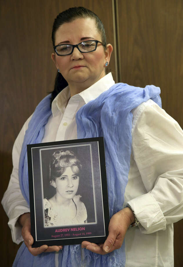 Sherri Nelson holds a picture of her late sister, Audrey Nelson, who was murdered by Samuel Little, during a news conference at Los Angeles Superior Court Thursday, Sept . 25, 2014. Little, 74, was sentenced to three consecutive terms of life in prison without parole for murdering three women in the late 1980s Little shouted out in court during his sentencing hearing that he didn't commit the killings and said he hoped for a new trial. His lawyer has filed a notice of appeal. (AP Photo/Nick Ut)