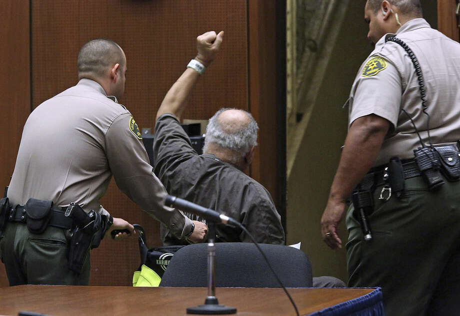 As family members of victims applaud and cheer, Samuel Little raises his fist as he is led out of the courtroom after being sentenced to three consecutive terms of life in prison without parole for murdering three women in the late 1980s, in a Los Angeles clourtroom Thursday, Sept. 25, 2014. Little, 74, shouted out in court during his sentencing hearing that he didn't commit the killings and said he hoped for a new trial. His lawyer has filed a notice of appeal. (AP Photo/Nick Ut)