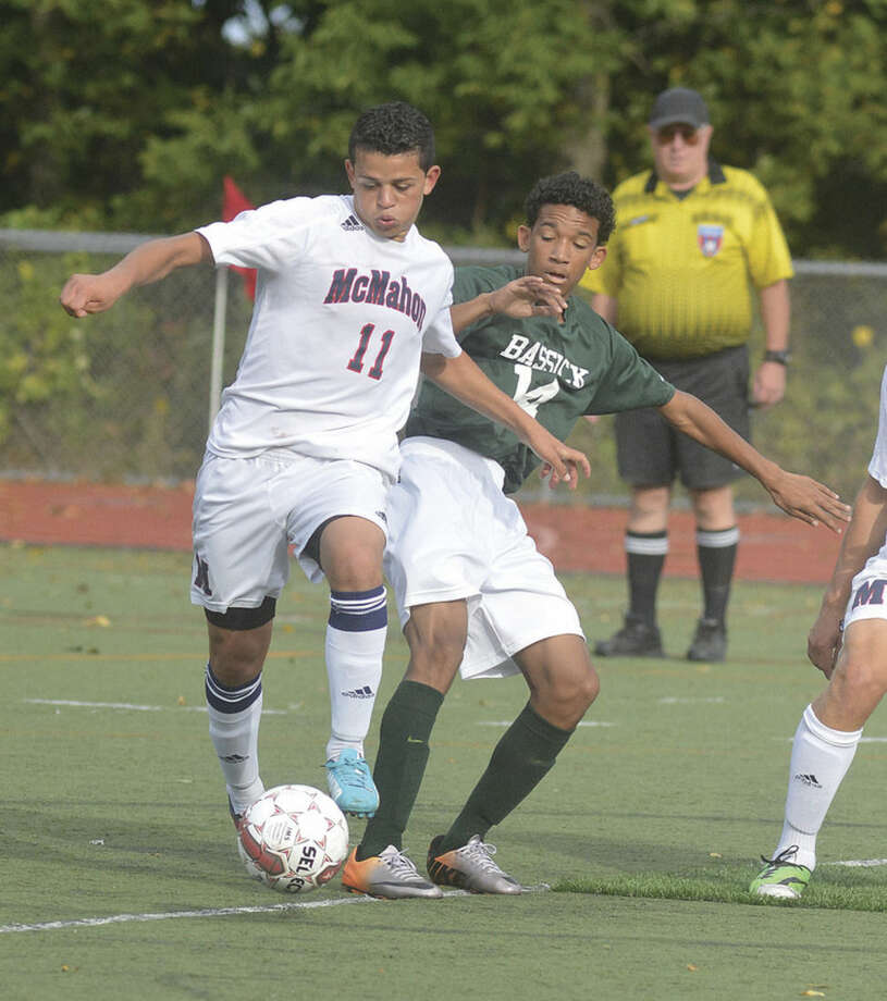 Hour Photo/Alex von KleydorffMcMahon's Christian Gutierrez (11) takes the ball off Bassick's Santiago Giraldo during Wednesday's game in Norwalk.