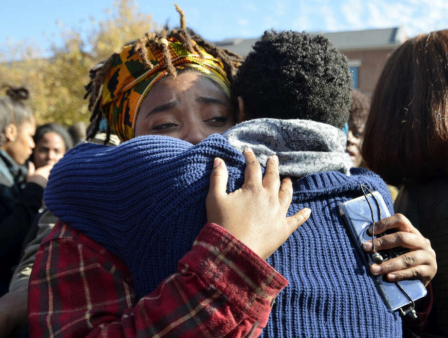Supporters embrace each other following the announcement that University of Missouri System President Tim Wolfe would resign Monday, Nov. 9, 2015, in Columbia, Mo. Wolfe resigned Monday with the football team and others on campus in open revolt over his handling of racial tensions at the school. (Halee Rock/Missourian via AP) MANDATORY CREDIT