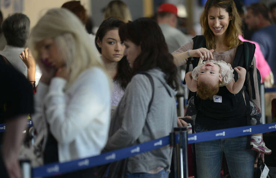 Ann Walden plays with her 15 month-old daughter Delphine while waiting in-line after their flight to Baton Rouge was delayed at O'Hare International Airport in Chicago, Friday, Sept. 26, 2014. All flights in and out of Chicago's two airports were halted Friday after a fire at a suburban air traffic control facility sent delays and cancellations rippling through the U.S. air travel network. Authorities said the blaze was intentionally set by a contract employee of the Federal Aviation Administration and had no ties to terrorism. (AP Photo/Paul Beaty)