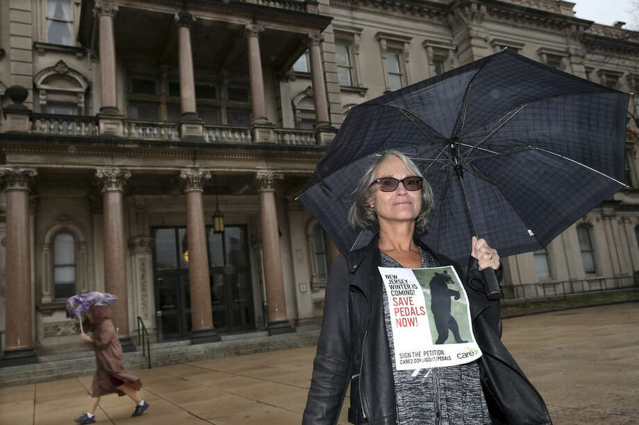 A woman holds a sign with a bear's photograph, as she stands near the Statehouse in the rain as she and other animal activists renewed their calls for New Jersey officials to help ensure the welfare of a bear that walks upright and has become a social media darling Tuesday, Nov. 10, 2015, Trenton, N.J. (AP Photo/Mel Evans)