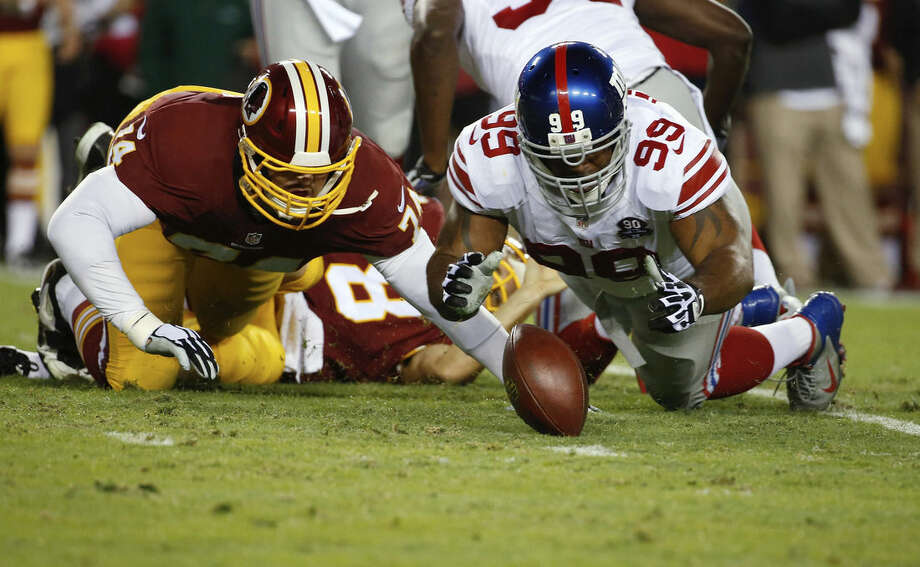 New York Giants defensive tackle Cullen Jenkins (99) falls on a loose ball as Washington Redskins tackle Tyler Polumbus (74) closes in after Redskins quarterback Kirk Cousins was sacked during the first half of an NFL football game in Landover, Md., Thursday, Sept. 25, 2014. The New York Giants recoved the fumble. (AP Photo/Alex Brandon)