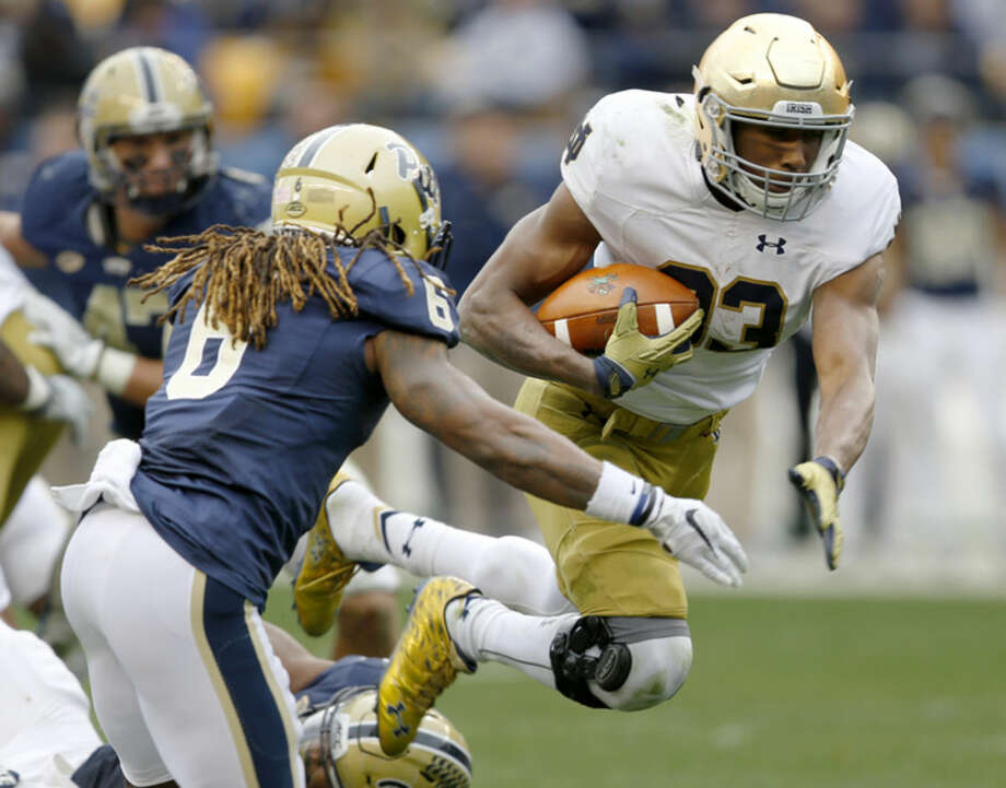 Notre Dame running back Josh Adams (33) runs past Pittsburgh defensive back Lafayette Pitts (6) for a first down in the fourth quarter of an NCAA football game, Saturday, Nov. 7, 2015 in Pittsburgh. Notre Dame won 42-30. (AP Photo/Keith Srakocic)