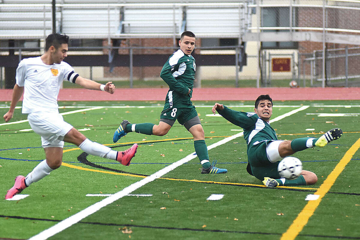 Hour photo/John Nash - Norwalk's Edward Mercuri, right, slides toward the ball in a vain effort to knock down a shot by South Windsor's Nicholas Heckt as the Bears' Andres Arias, center, looks on.