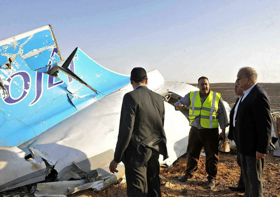 FILE - In this Saturday, Oct. 31, 2015, file photo released by the Prime Minister's office, Egyptian Prime Minister Sherif Ismail, right, looks at the remains of a crashed Russian passenger jet in Hassana, Egypt. Egyptian media have reacted with fury as Britain and the U.S. increasingly point to a bomb as the cause of the Russian plane crash, and many have hammered home to the public that their country is facing a Western conspiracy to scare off tourists and destroy the economy. (Suliman el-Oteify/Egyptian Prime Minister's Office via AP, File)
