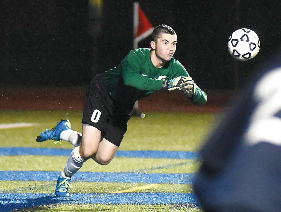 Hour photo/John Nash - Staples goalkeeper Brenden Price lunges forward to punch out a ball during Tuesday's CIAC Class LL first round game against Hall in West Hartford.