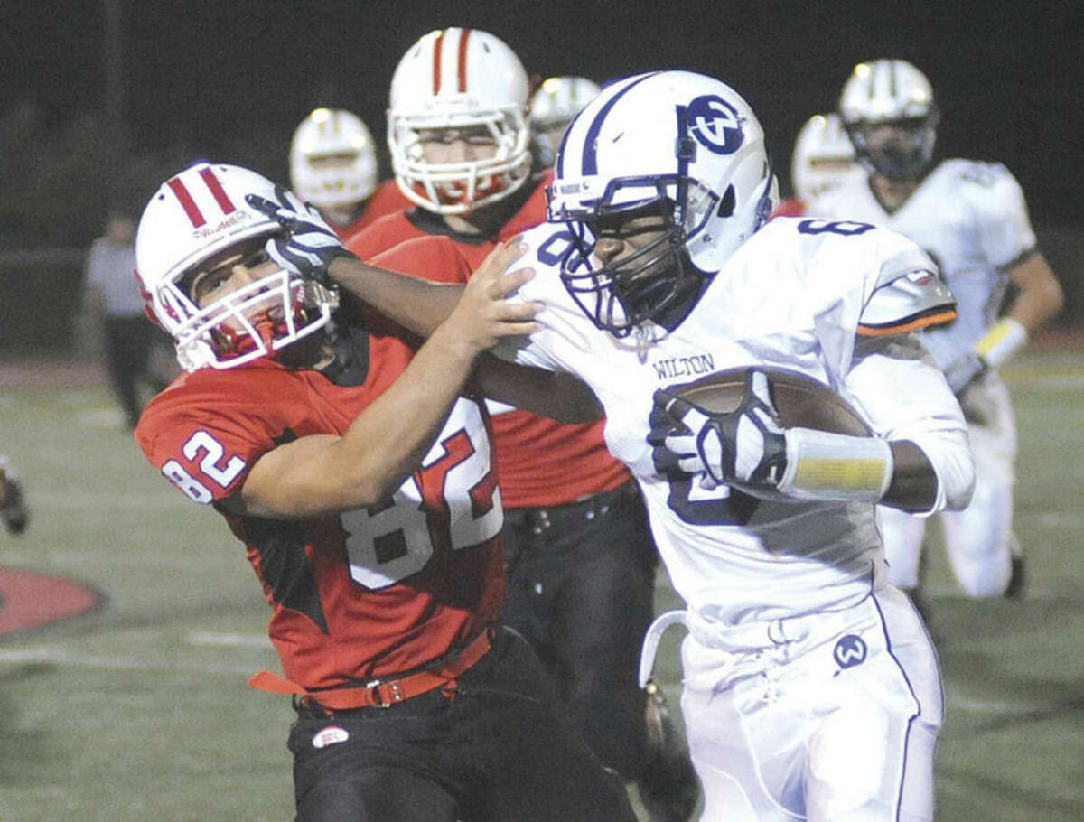 Hour photo/John Nash Wilton's Rod-Djaly Thoby, right, tries to hold off a Branford tackler during Friday night's game in Branford.