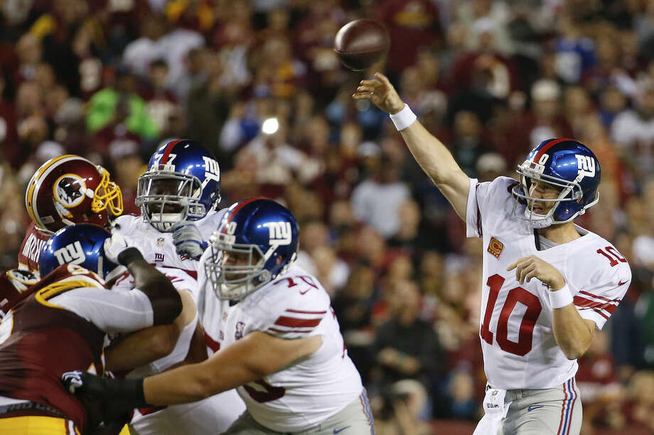 New York Giants quarterback Eli Manning (10) passes the ball during the first half of an NFL football game against the Washington Redskins in Landover, Md., Thursday, Sept. 25, 2014. (AP Photo/Alex Brandon)