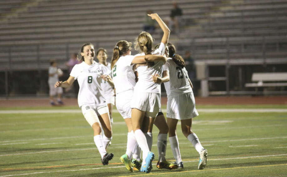 Hour photo/Danielle CallowayNorwalk's Hannah Froelich, front, celebrates with teammates after scoring the Bears' first goal against Trinity Catholic at Norwalk High School Friday night.