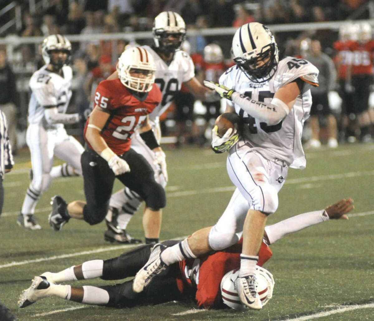 Hour photo/John Nash Wilton's T.J. Savvaides runs over a Branford tackler en route to a long gain during Friday's football game in Branford. Wilton won 34-7.