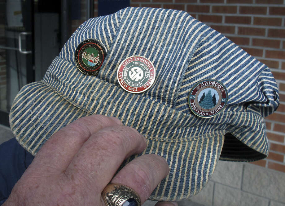 In this Saturday Nov. 7, 2015 photo, Jack Gaffey, of Kensington, Md., displays the pins on his railroad engineer's cap in Rutland, Vt. Gaffey and his wife traveled to Vermont to ride the Roots on the Rails music train on its first East Coast excursion between Bellows Falls and Rutland. About 50 passengers spent the day listening to music while riding in vintage rail cars of the Green Mountain Express rolling through the countryside. (AP Photo/Wilson Ring)