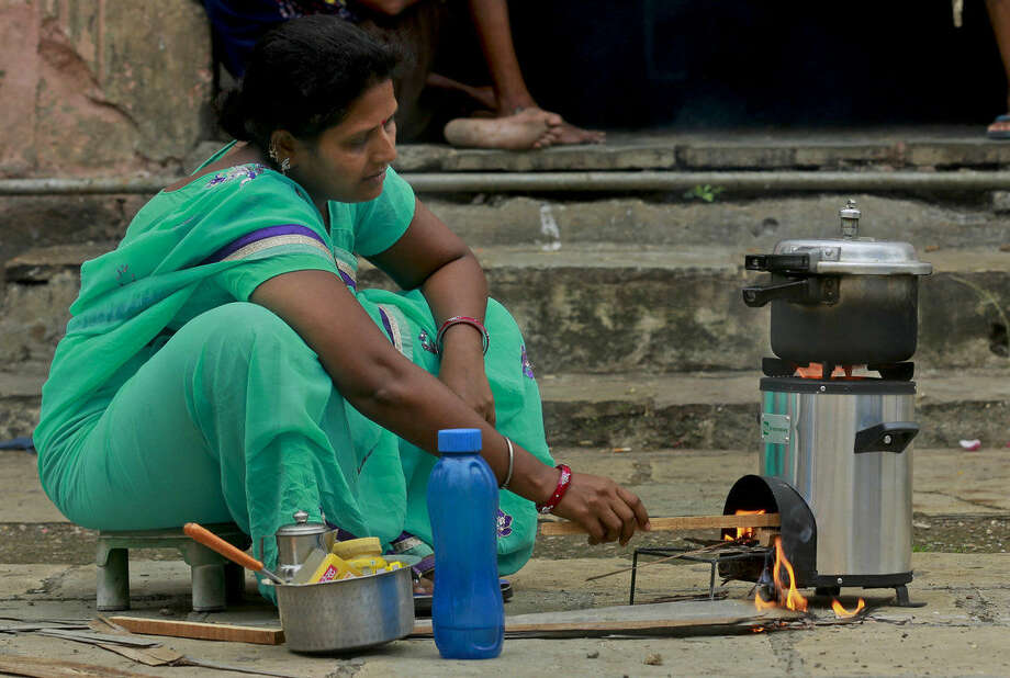"""In this Oct 27, 2015 photo, Hansa Arjun 36, an employee of cookstove developer Greenway Appliances, demonstrates the use of Biomass stove in Mumbai, India. India - far behind the industrialized world in economic and infrastructure development - says helping people shift to cleaner cooking technologies is part of its overall strategy for combating climate change. """"India is a peculiar market. You go into a typical household, and they will have a TV, a couple of mobile phones. And yet somehow the kitchen is still 50 years behind the rest of the house,"""" said Neha Juneja, co-founder and CEO of Greenway Appliances. (AP Photo/Rafiq Maqbool)"""