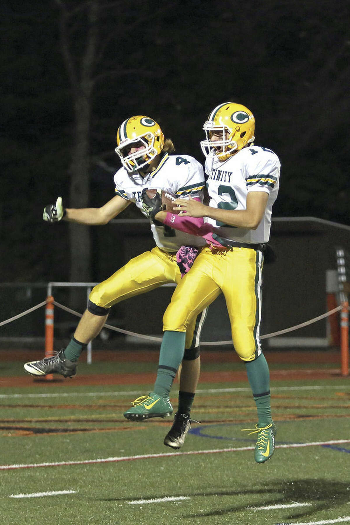 Photo by Danielle Calloway Trinity Catholic's Johnny Somers, left, is congratulated by quarterback Anthony Lombardi after scoring a touchdown during a game against Stamford High School at Boyle Stadium Friday evening.