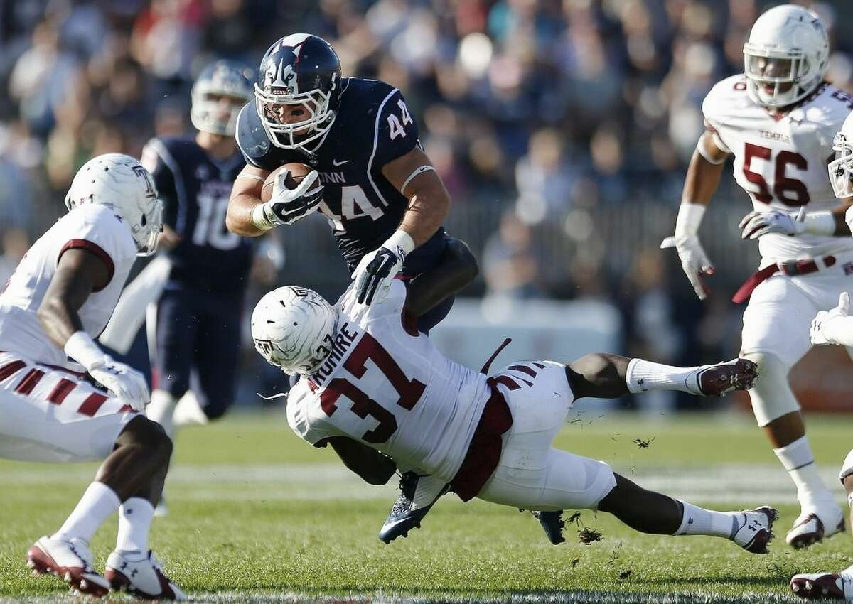 Temple defensive back Boye Aromire (37) tackles Connecticut running back Max DeLorenzo (44) during the first quarter of an NCAA college football game in East Hartford, Conn., Saturday, Sept. 27, 2014. (AP Photo/Michael Dwyer)