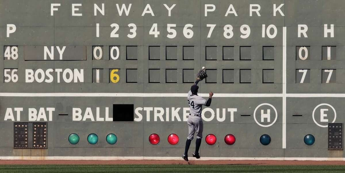 New York Yankees left fielder Chris Young plays an RBI double by Boston Red Sox's Garin Cecchini off the Green Monster scoreboard during the second inning of a baseball game at Fenway Park in Boston, Saturday, Sept. 27, 2014. (AP Photo/Charles Krupa)