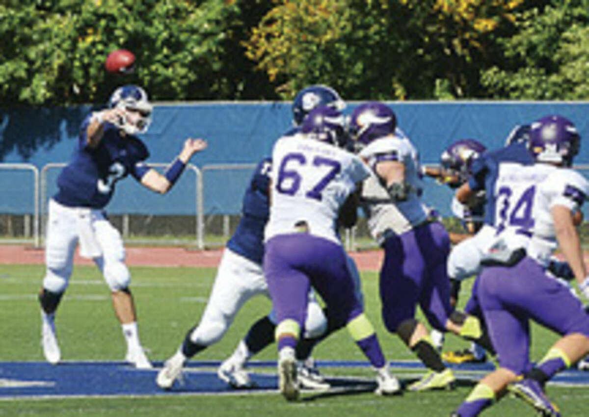Hour photo/Erik Trautmann Staples quarterback Teddy Coogan throws down field during Saturday's game against Westhill.