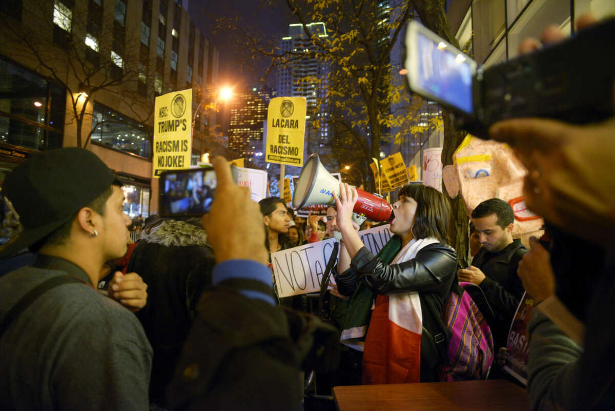 Karina Garcia, of the ANSWER Coalition, uses a megaphone to lead demonstrators in a chant during a protest against Republican presidential candidate Donald Trump's hosting