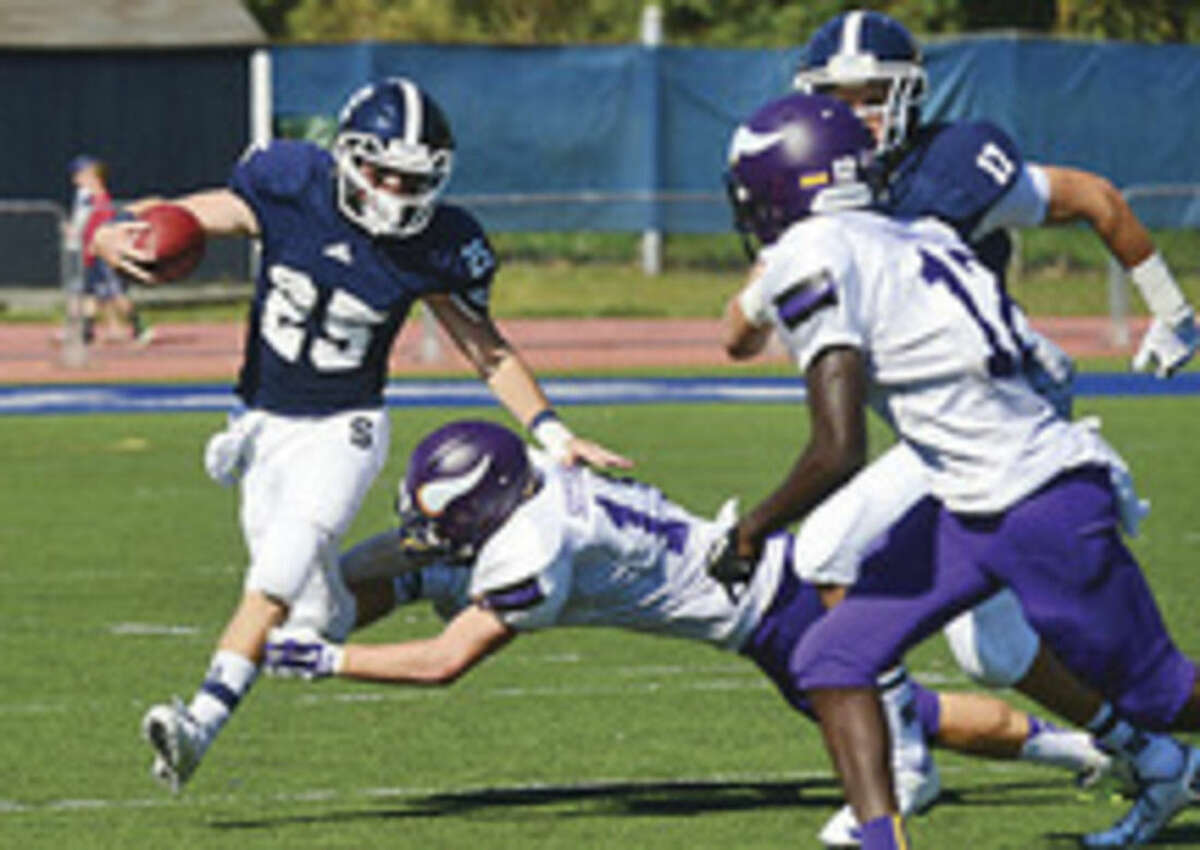 Hour photo/Erik Trautmann Staples running back Ethan Burger breaks a tackle during the Wreckers' game Saturday afternoon against Westhill in Westport.