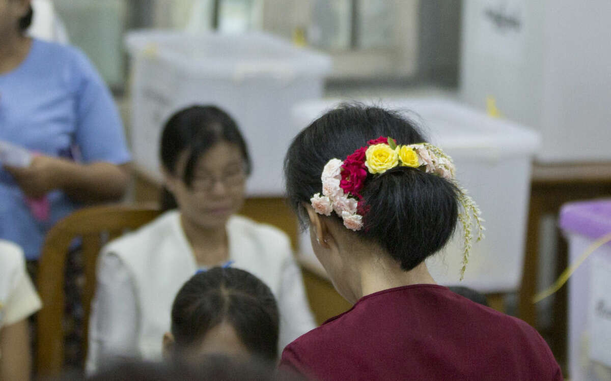 Leader of Myanmar's National League for Democracy Aung San Suu Kyi, with flowers in back of her hair, stands at a desk of a polling official at a polling station in Yangon, Myanmar, Sunday, Nov. 8, 2015. Myanmar voted Sunday in historic elections that will test whether popular mandate will help loosen the military's longstanding hold on power even if opposition leader Suu Kyi's party secures a widely-expected victory. (AP Photo/Gemunu Amarasinghe)