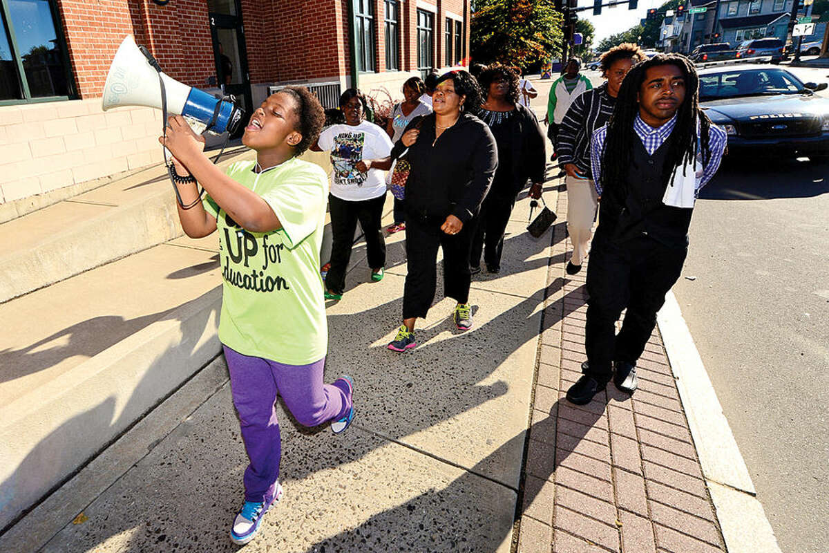 Hour photo / Erik Trautmann Loacl residents including Janya Adonai, left, take part in a prayer walk Saturday mornng to kick off the educational forum, Ferguson in Connecticut. The walk began at the Norwalk police station and ended at Nathaniel Ely School.