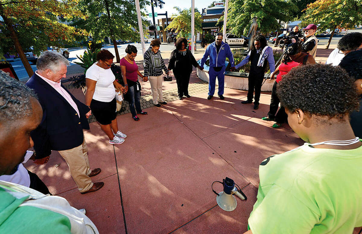 Hour photo / Erik Trautmann Loacl residents take part in a prayer walk Saturday morning to kick off the educational forum, Ferguson in Connecticut. The walk began at the Norwalk police station and ended at Nathaniel Ely School.