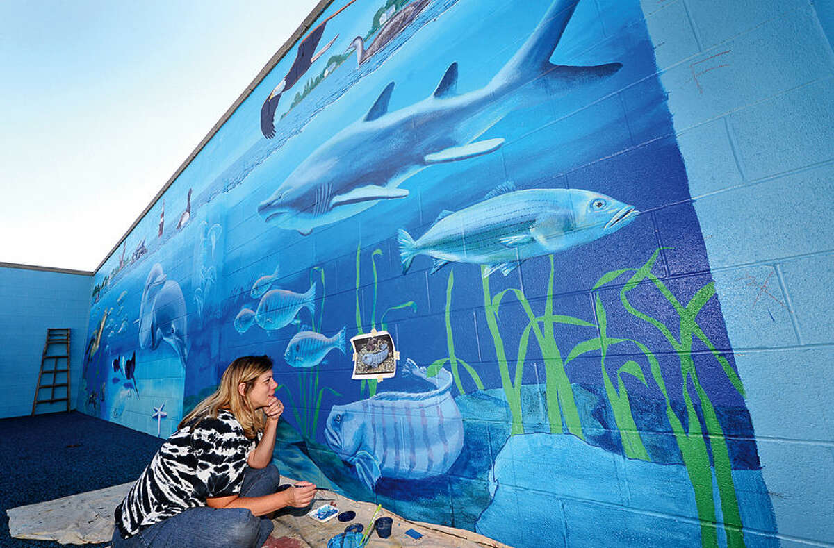 Hour photo / Erik Trautmann Artist Lorraine Gelard paints a aquatic life mural in the enclosed Parrot Cove area at Calf Pasture Beach Friday. The area will serve children and educational programs at the beach.